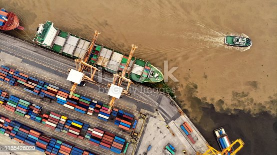 istock Logistics and transportation of Container Cargo ship and Cargo plane with working crane bridge in shipyard, logistic import export and transport industry background 1135428029