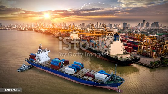 istock Logistics and transportation of Container Cargo ship and Cargo plane with working crane bridge in shipyard at sunrise, logistic import export and transport industry background 1135428102