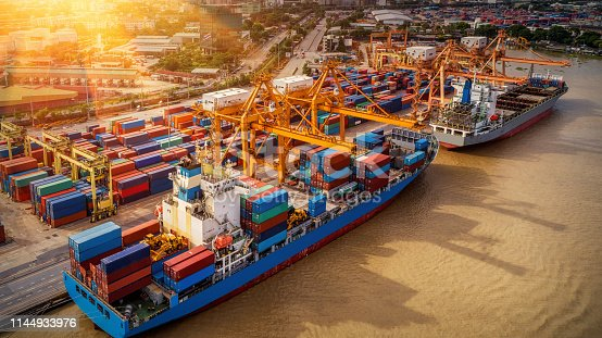 istock Logistics and transportation of Container Cargo ship and Cargo plane with working crane bridge in shipyard at sunrise, logistic import export and transport industry background 1144933976