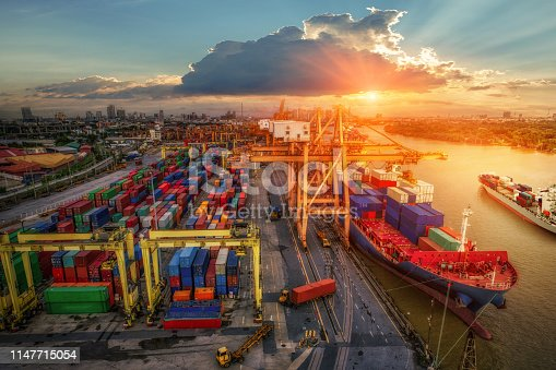 istock Logistics and transportation of Container Cargo ship and Cargo plane with working crane bridge in shipyard at sunrise, logistic import export and transport industry background 1147715054