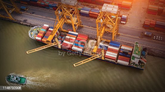 istock Logistics and transportation of Container Cargo ship and Cargo plane with working crane bridge in shipyard at sunrise, logistic import export and transport industry background 1148732008