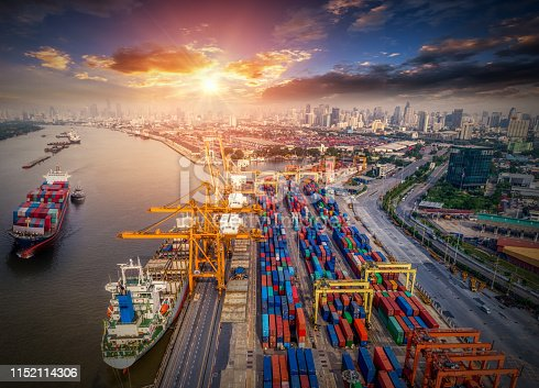 istock Logistics and transportation of Container Cargo ship and Cargo plane with working crane bridge in shipyard at sunrise, logistic import export and transport industry background 1152114306