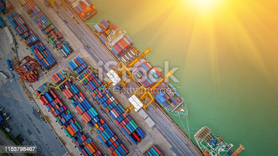 istock Logistics and transportation of Container Cargo ship and Cargo plane with working crane bridge in shipyard at sunrise, logistic import export and transport industry background 1153798467
