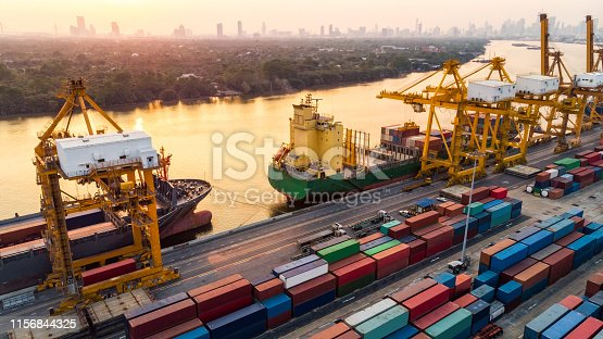 istock Logistics and transportation of Container Cargo ship and Cargo plane with working crane bridge in shipyard at sunset, logistic import export and transport industry background 1156844325