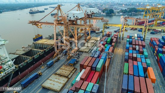 istock Logistics and transportation of Container Cargo ship and Cargo plane with working crane bridge in shipyard, logistic import export and transport industry background 1156844337