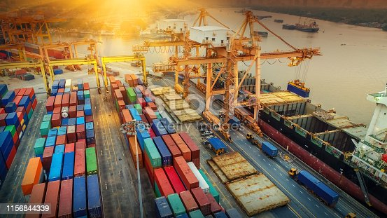 istock Logistics and transportation of Container Cargo ship and Cargo plane with working crane bridge in shipyard at sunset, logistic import export and transport industry background 1156844339