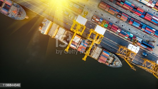 istock Logistics and transportation of Container Cargo ship and Cargo plane with working crane bridge in shipyard at sunset, logistic import export and transport industry background 1156844340