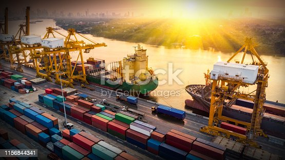 istock Logistics and transportation of Container Cargo ship and Cargo plane with working crane bridge in shipyard at sunset, logistic import export and transport industry background 1156844341