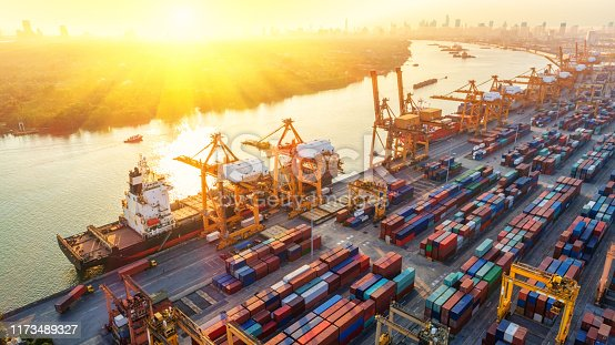 istock Logistics and transportation of Container Cargo ship and Cargo plane with working crane bridge in shipyard at sunrise, logistic import export and transport industry background 1173489327