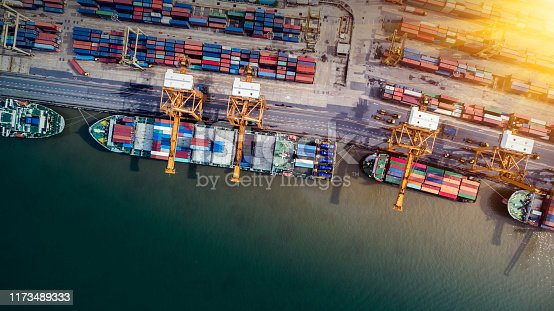 istock Logistics and transportation of Container Cargo ship and Cargo plane with working crane bridge in shipyard at sunrise, logistic import export and transport industry background 1173489333