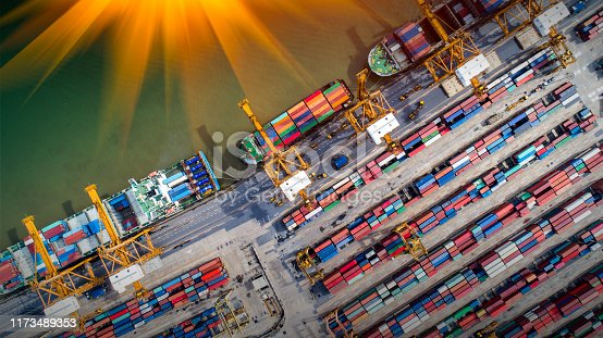 istock Logistics and transportation of Container Cargo ship and Cargo plane with working crane bridge in shipyard at sunrise, logistic import export and transport industry background 1173489353