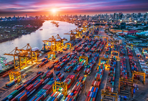 Logistics And Transportation Of Container Cargo Ship And Cargo Plane With Working Crane Bridge In Shipyard At Sunrise Logistic Import Export And Transport Industry Background Stock Photo - Download Image Now