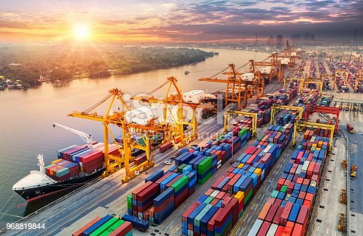 istock Logistics and transportation of Container Cargo ship and Cargo plane with working crane bridge in shipyard at sunrise, logistic import export and transport industry background 968819844