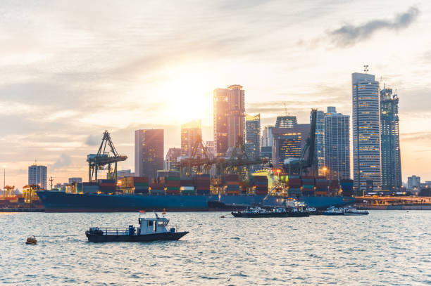 Logistics and transportation of Container Cargo ship and Cargo with working crane bridge in shipyard at sunrise, logistic import export and transport industry background stock photo