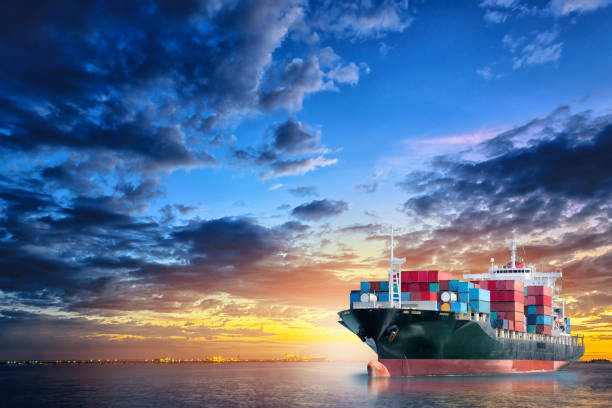 Logistics and transportation of International Container Cargo ship in the ocean at twilight sky, Freight Transportation, Shipping stock photo