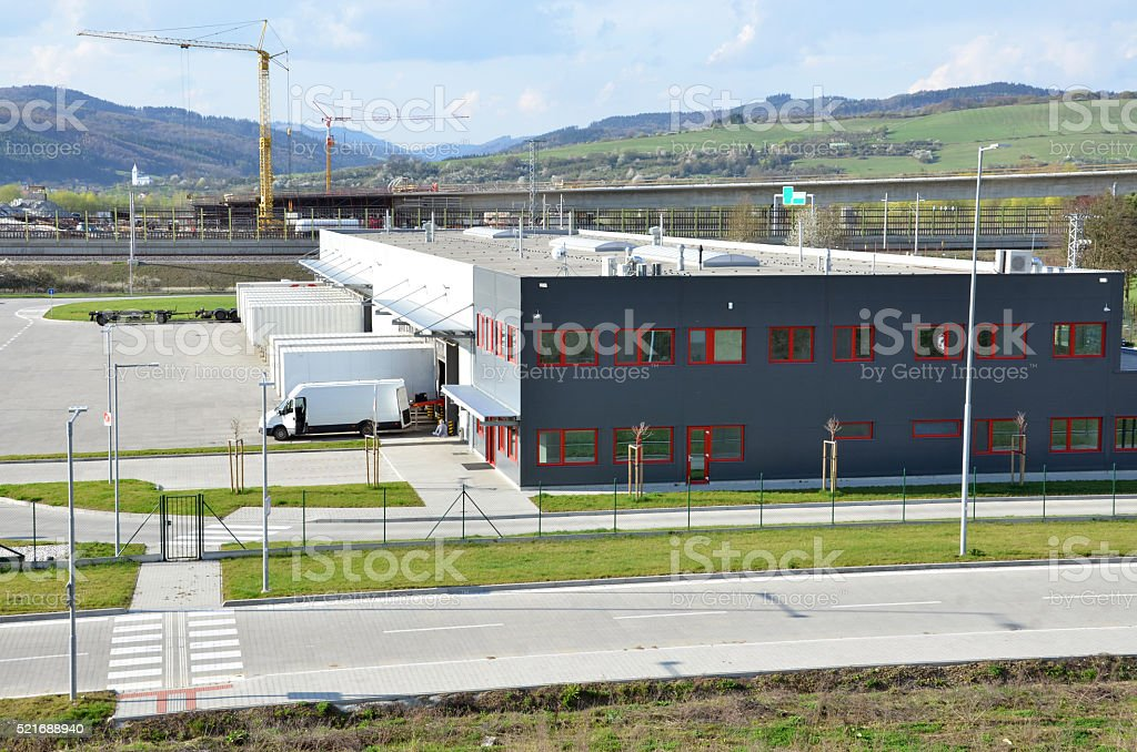 Logistics center, freight uncharged from van. Tower cranes in background stock photo
