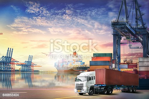 693774520 istock photo Logistics import export background and transport industry of Container truck and Cargo ship with working crane bridge in shipyard at sunset sky 646853404