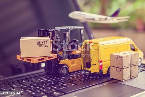 641289780 istock photo Logistics, supply chain and delivery service concept : Fork-lift truck moves a pallet with box carton. Van on a laptop computer, depicts wide spread of products around globe in ecommerce popular era 1193265314