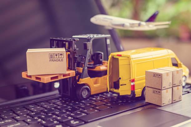 물류, 공급망 및 배송 서비스 개념 : 포크 리프트 트럭은 상자 판지와 팔레트를 이동합니다. 노트북 컴퓨터에 밴, 전자 상거래 인기 시대에 전 세계 제품의 넓은 확산을 묘사 - 취급 주의 표지판 뉴스 사진 이미지