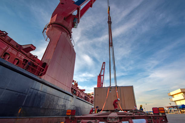 Logistics sustem Package unit of the heavy life cargo being discharging or loading by the ship crane under supervisor by professional handling in the port terminal hooikoorts stock pictures, royalty-free photos & images