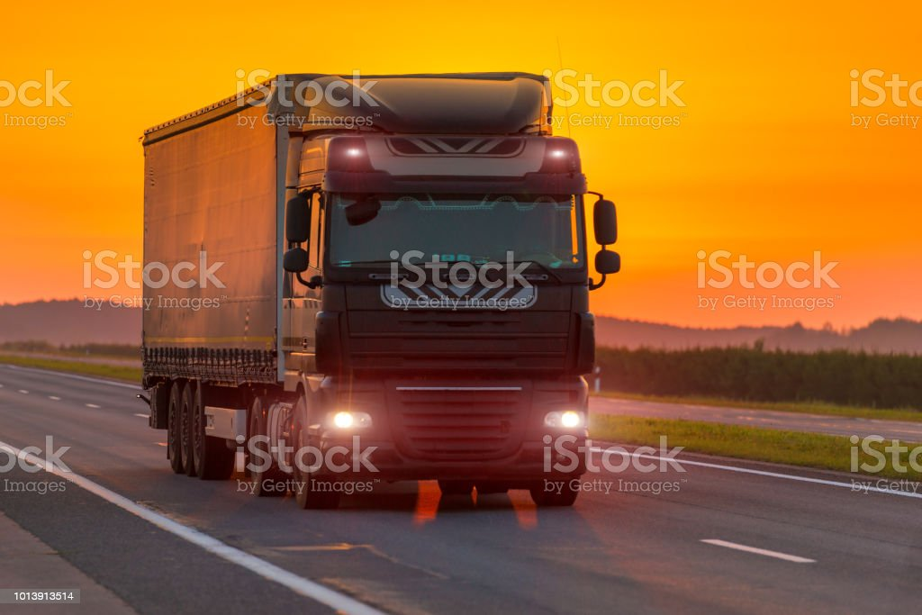 logistics truck on the highway at dawn, orange sky stock photo