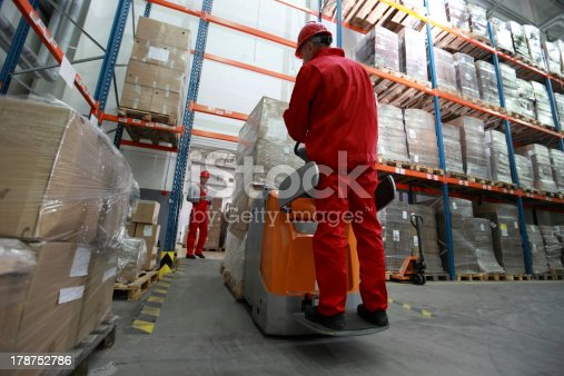 istock logistics - two workers working in storehouse with forklift loader 178752786