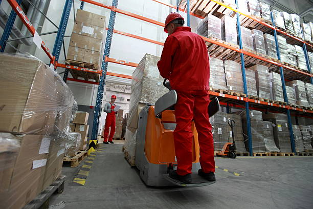 logistics - two workers working in storehouse with forklift loader stock photo