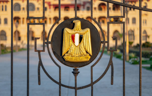 Logo of Egypt on an iron fence revealing Montaza Presidential Palace, consists of Golden Eagle of Saladin holding a scroll with the name of the republic and a shield with the flag's colors stock photo