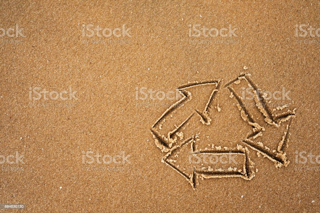 Logo of recycling drawing on sand on seashore. stock photo