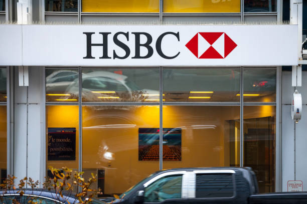 Logo of the HSBC Bank, on their main branch in Montreal with cars passing by. HSBC is a british bank spread worldwide Picture of a sign with the logo of the HSBC Bank on its local branch in Montreal, Quebec. HSBC Bankis a british Financial institution, one of the largest banking and financial services organisations in the world. hsbc stock pictures, royalty-free photos & images