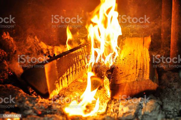 Photo of logs and woods are burning with a large fire on the ashes and coals in the stove. fire close-up