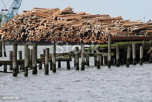 Redwood logs on barge in Humboldt Bay in northern California being off-loaded by crane at mill