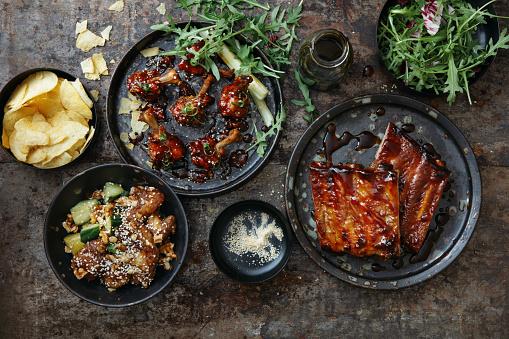 BBQ lollipop chicken wings with spicy BBQ glaze. Spicy glazed pork ribs. Tempura pork with vegetables. Flat lay top-down composition on dark background.