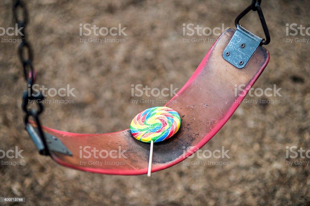 Lollipop sitting alone on a swing stock photo