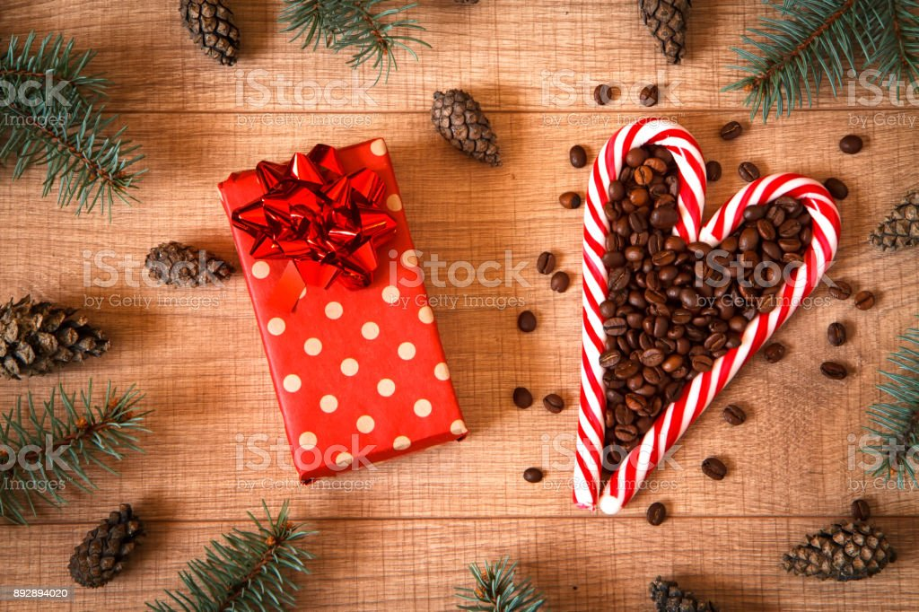 A lollipops composition with coffee beans, New Year / Christmas tree, cones, gift in package and cones on the wooden background template stock photo