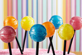 A close up of different colored lollipops on sticks