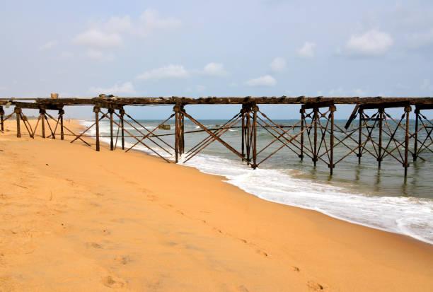 lomé, togo: downtown beach aliong boulevard de la république - old rusting pier - république photos et images de collection