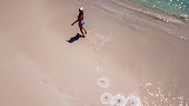 A girl in bikini and straw hat walking on a wet sand, leaving the footprints behind her. Pink Beach in Lombok, Indonesia. Girl is happing, enjoying the beautiful beach. Drone shot taken from above.