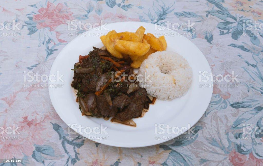 Lomo Saltado (Peruvian Stir-Fried Beef) with French fries stock photo