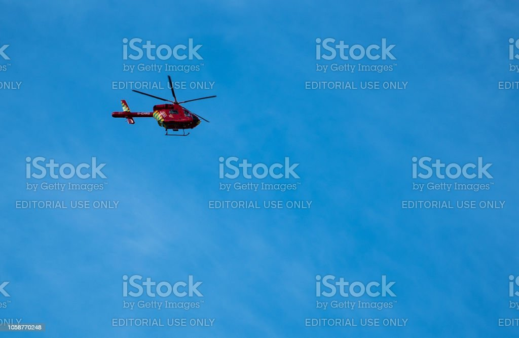London Air Ambulance Helicopter G-EHMS flying through the blue sky above the Capital City stock photo