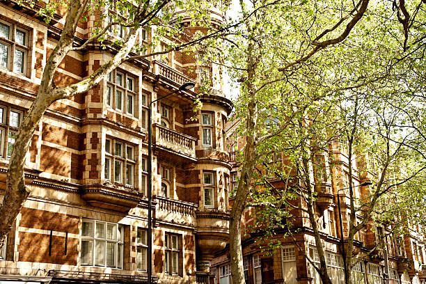 london architecture: classic facade with lush trees in summer day stock photo