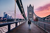 Young man with backpack walking on Tower Bridge against cityscape with skyscrapes at colorful sunrise. London, United Kingdom
