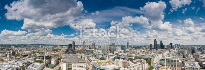 Blue skies and dramatic cloudscape over the skyscrapers and canyons of the City of London, from the Barbican, past the Bank of England and landmark towers of the downtown district, across the River Thames to City Hall. ProPhoto RGB profile for maximum color fidelity and gamut.