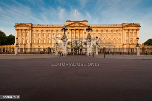 London, UK - May 3th, 2011: Warm dawn sunlight illuminated the Portland stone facade, windows, balcony and ornate entrance gates of Buckingham Palace, London residence of the British Monarch, from the Victoria Memorial on The Mall.