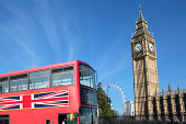 Traditional red double decker bus with Big Ben in the background.  Millenium wheel in the far distance.  Sharp focus on Big Ben.  Bus in the foreground has slight motion blur.  Alternative file with traditional telephone box shown below: