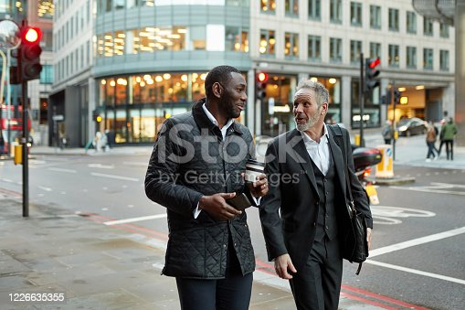 African and Caucasian businessmen in 40s and 50s walking side by side and talking at end of workday in financial district.