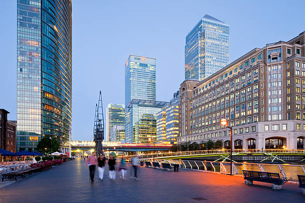 London, Canary Wharf, Great Britain London, Great Britain - August 30, 2010. The commercial district Canary Wharf at night. The illuminated skyline with high-rise buildings in the background. A group of people in front take a walk in the small harbor area, enjoying the warm summer afternoon. Photo taken with 24mm tilt and shift lenses. hsbc stock pictures, royalty-free photos & images