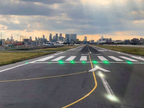 London Canary Wharf visible from Runway 27 of London City Airport London, United Kingdom - 12 July 2019: London's financial district of Canary Wharf is visible right in the extension of Runway 27 of London City Airport (LCY). air transport building stock pictures, royalty-free photos & images