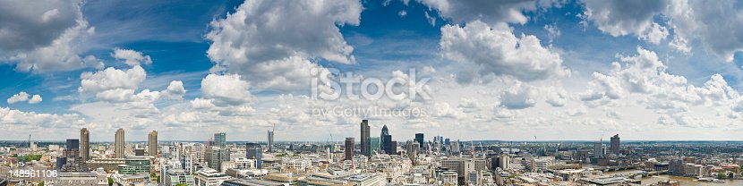 Big skies and white fluffy clouds over a sweeping panoramic vista across the skyscrapers, streets and landmarks of the City of London, the UK's financial and business centre, from the Barbican, past the iconic towers around the Bank of England and the skyscrapers of Canary Wharf and Docklands, to the banks of the Thames, Tower Bridge, City Hall, Shakespear's Globe Theatre and the distant aerials of Crystal Palace. ProPhoto RGB profile for maximum color fidelity and gamut.