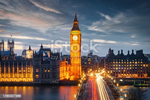 Aerial view along the busy street and traffic on Westminster Bridge, illuminated Big Ben and the Houses of Parliament. Motion Blured Car Lights. Twilight - Night Scene under vibrant skyscape. London City, United Kingdom, Europe